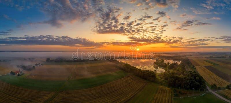 Mistige ochtend bij een meer in Beieren Duitsland terwijl de zon toeneemt stock fotografie