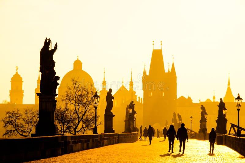 Mistige ochtend op Charles Bridge, Praag, Tsjechische Republiek Zonsopgang met silhouetten van lopende mensen, standbeelden en Ou stock fotografie