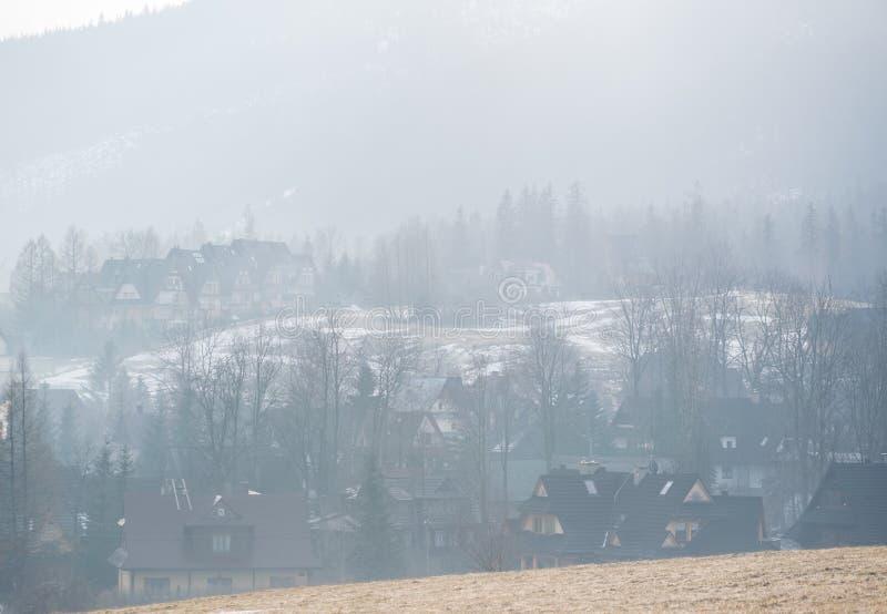 Mistige ochtendmist over bergvallei met landelijke landbouwbedrijfwoningbouw stock afbeelding