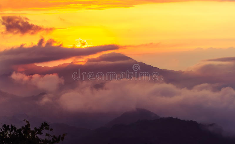 Mistige oranje zonsondergang in de bergen stock afbeelding