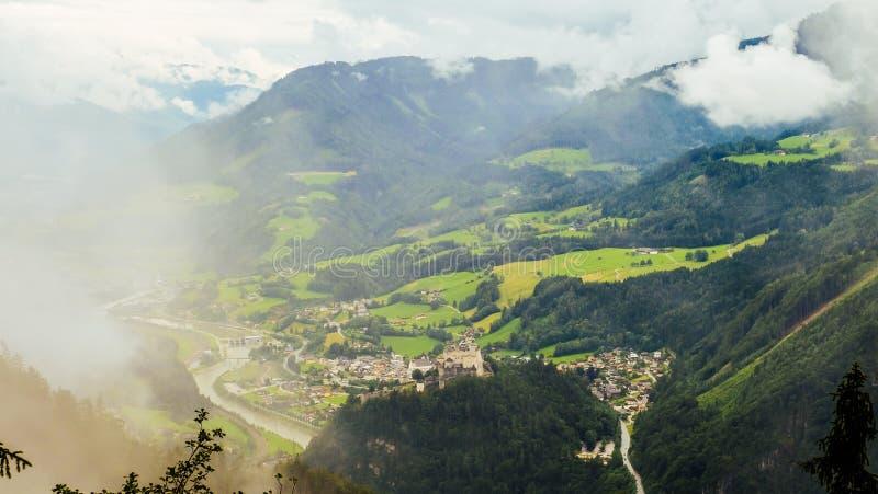 Mistige scène van Hohenwerfen-kasteel onder bergketens, Oostenrijk royalty-vrije stock foto's