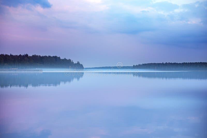 Mistige vroege ochtendzonsopgang op een spiegel opgedoken meer stock afbeeldingen