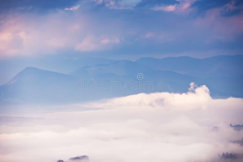 Mistige zonnige ochtend in berg Nevelige Heuvels Stad in vallei royalty-vrije stock fotografie