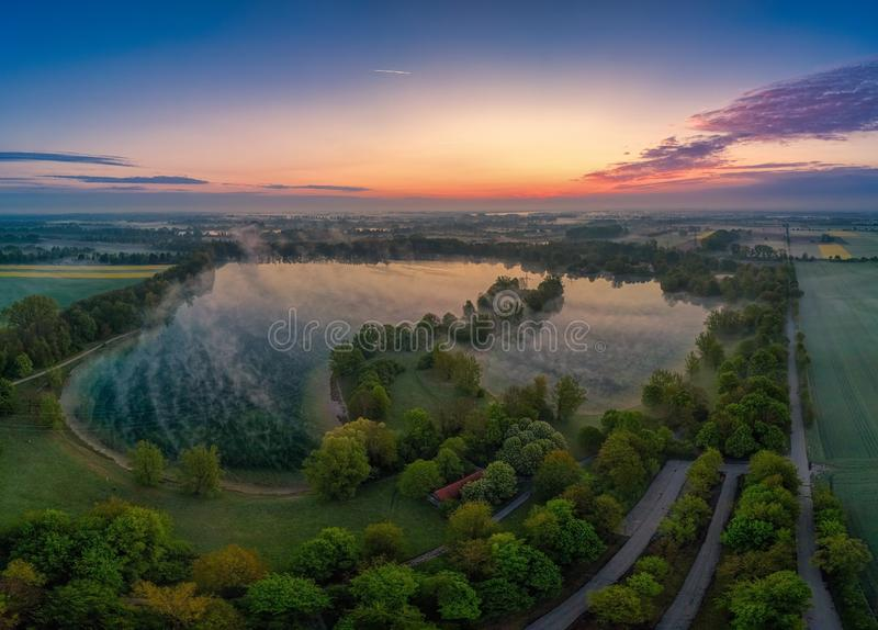 Mistige zonsopgang vroege ochtend bij een meer stock fotografie