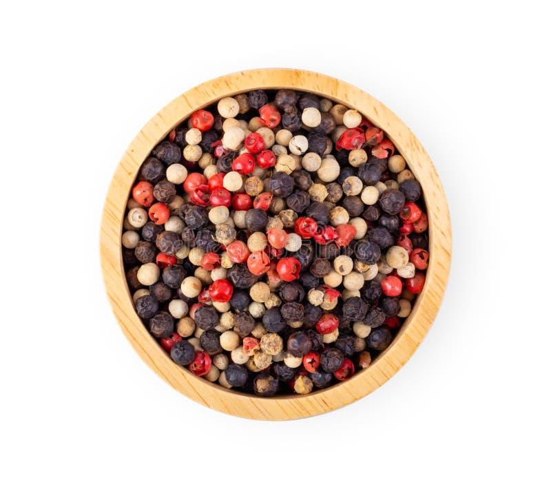 Misto dei peperoni caldi, rosso, nero, bianco in ciotola di legno isolata su bianco fotografia stock