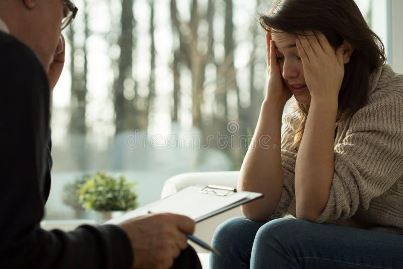 Mistroostig meisje tijdens psychotherapiezitting stock fotografie