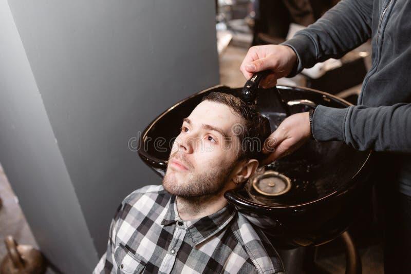 Mistrz myje głowę klient w fryzjera męskiego sklepie, fryzjer robi fryzurze dla młodego człowieka obraz royalty free