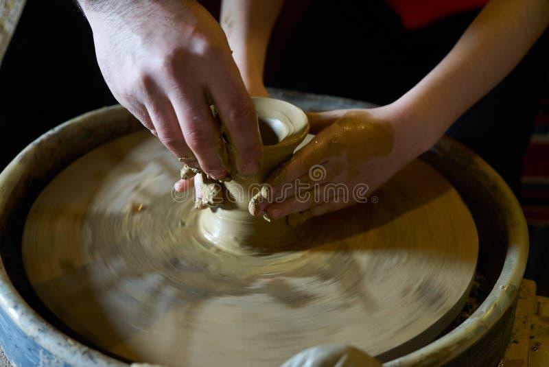 Mistrz pomaga dziecka robić garnkowi glina na ceramicznym kole, zdjęcie stock