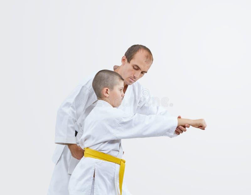 Mistrz uczy atlety z żółtym paskiem bić cios zdjęcie royalty free