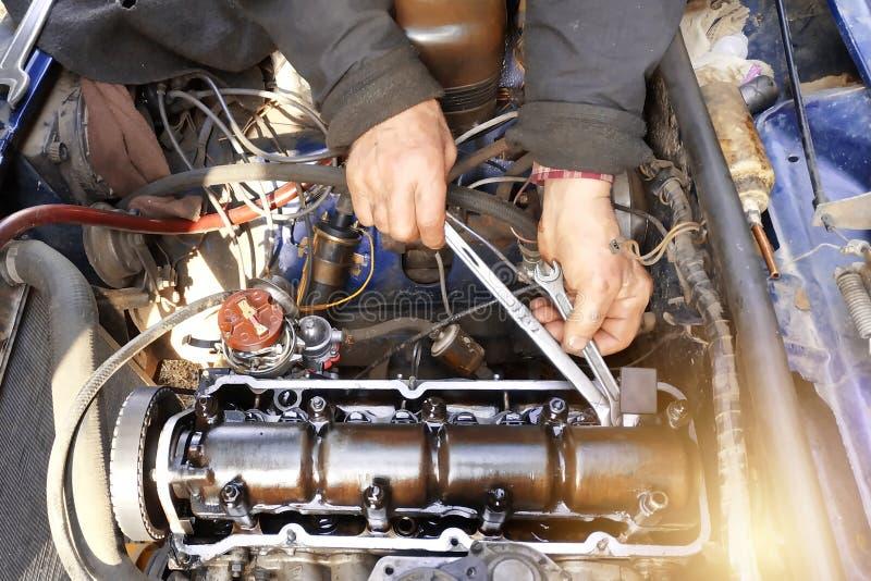 Mistrz w garażu stuka klapy w starym samochodzie, stary za samochodzie obrazy stock