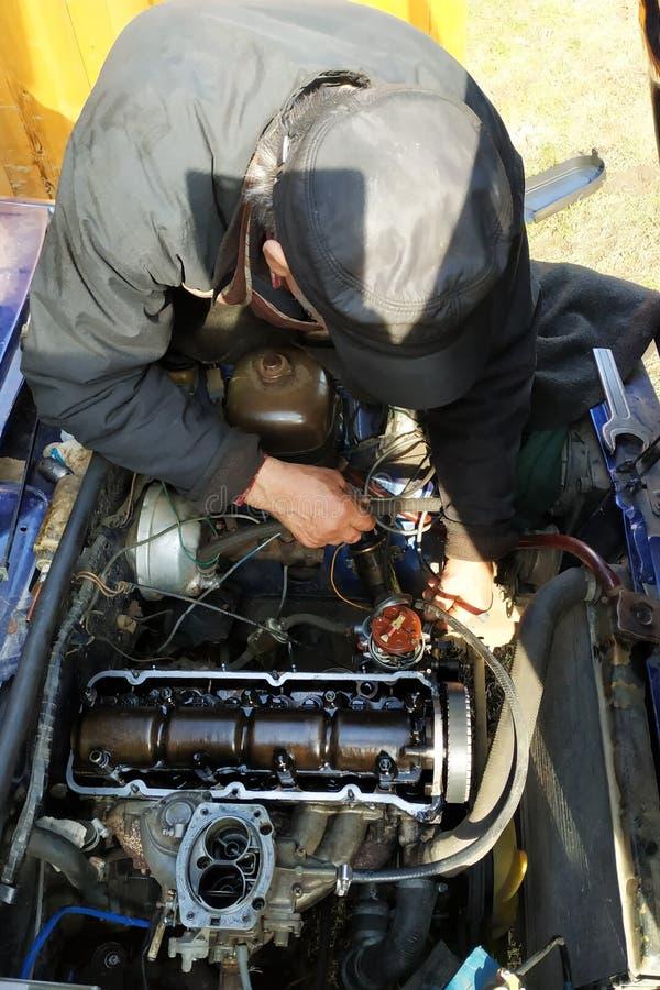 Mistrz w garażu stuka klapy w starym samochodzie, VAZ samochód, stary za samochodzie zdjęcia stock