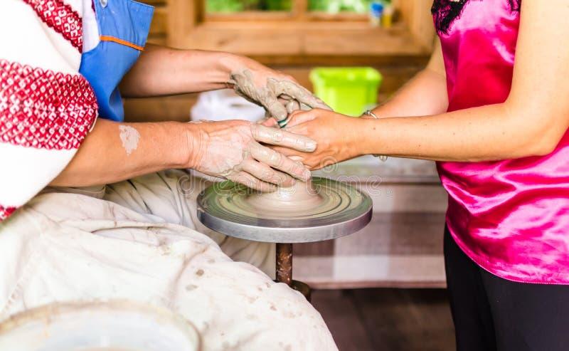 Mistrza i aplikanta uczenie gliniany wykonywać ręcznie garncarka i kobiet ręki, zdjęcie stock
