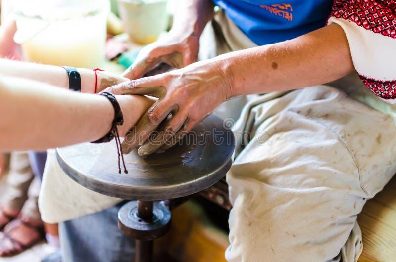 Mistrza i aplikanta uczenie gliniany wykonywać ręcznie garncarka i kobiet ręki, zdjęcia royalty free