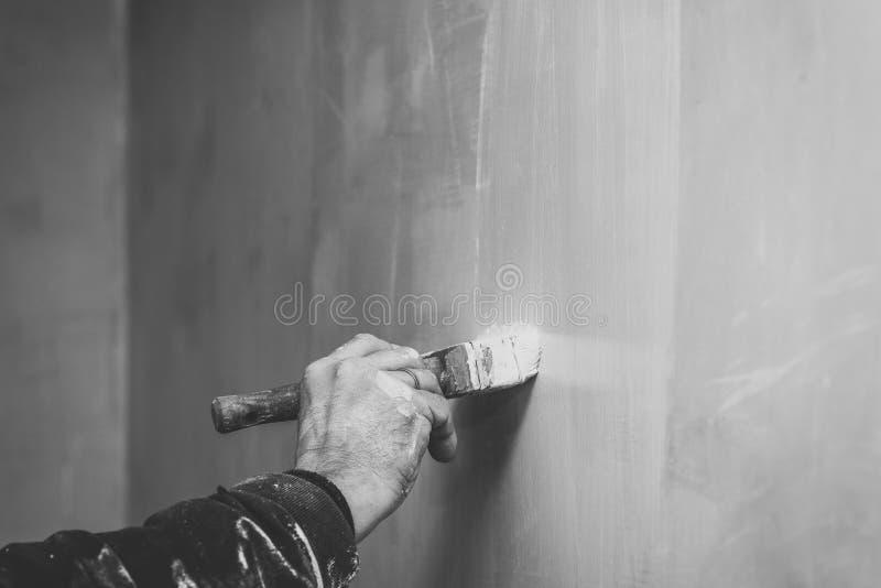 Mistrzowska prima kit ściana przed stosować dekoracyjną warstwę tynk pracuje w domu, druga scena, bezbarwny retro, naprawy fotografia royalty free