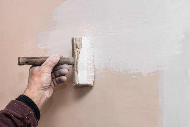 Mistrzowska prima kit ściana przed stosować dekoracyjną warstwę tynk pracuje w domu, druga scena, naprawy obraz royalty free