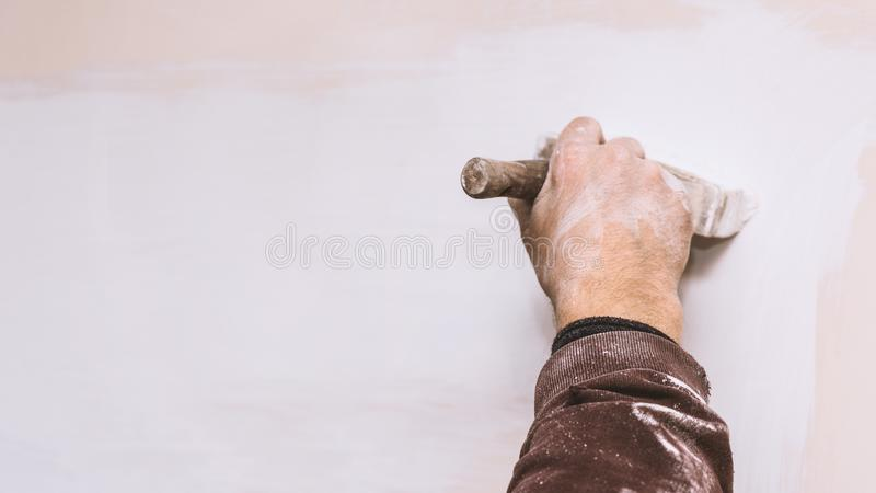 Mistrzowska prima kit ściana przed stosować dekoracyjną warstwę tynk pracuje w domu, druga scena, naprawy fotografia stock