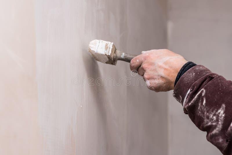 Mistrzowska prima kit ściana przed stosować dekoracyjną warstwę tynk pracuje w domu, druga scena, naprawy zdjęcia royalty free