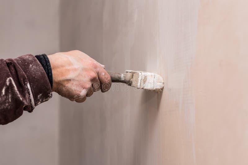 Mistrzowska prima kit ściana przed stosować dekoracyjną warstwę tynk pracuje w domu, druga scena, naprawy obrazy stock