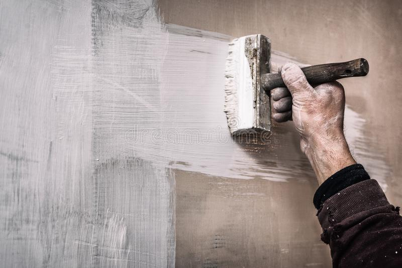 Mistrzowska prima kit ściana przed stosować dekoracyjną warstwę tynk pracuje w domu, druga scena, z hałasu skutkiem, naprawy fotografia stock