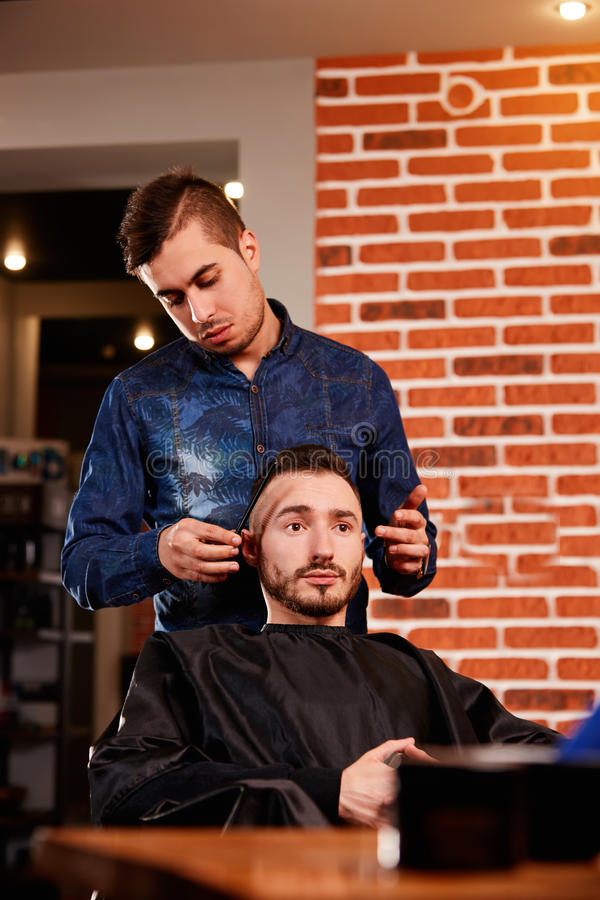 Mistrzowski zgrzywiony włosy mężczyzna w zakładzie fryzjerskim, fryzjer robi fryzurze dla młodego człowieka fotografia royalty free