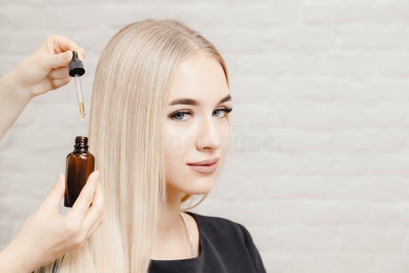 Mistrzowskiego fryzjer procedury oleju w?osiany traktowanie dla kobiety Poj?cie zdroju salon obraz stock