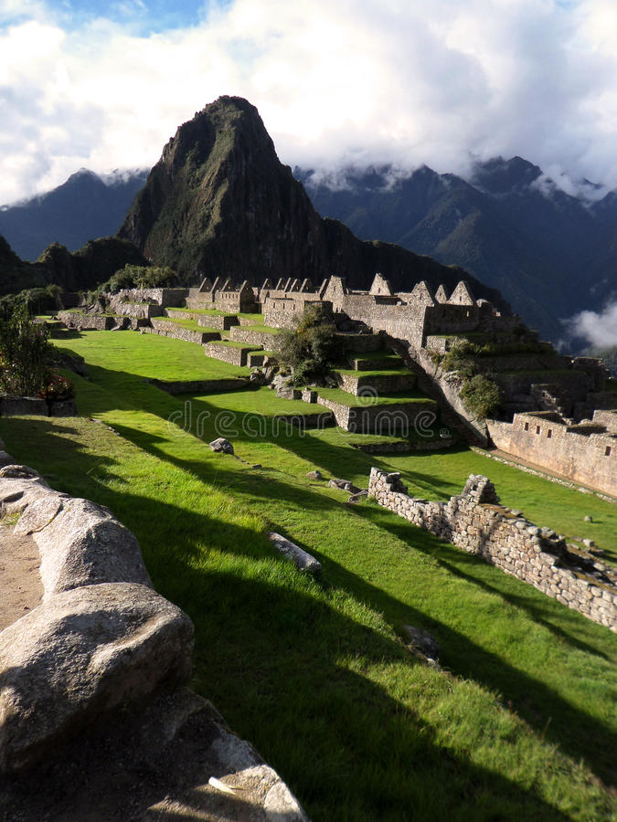 Mists of Machu Picchu. View of the main plaza complex of Machu Picchu with the peak of Wayna Picchu towering in the distance as the mists of late afternoon royalty free stock photo