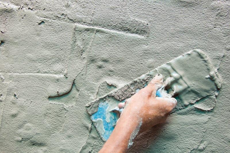 Mistura concreta fresca da mão do pedreiro do close up com pá de pedreiro fotos de stock