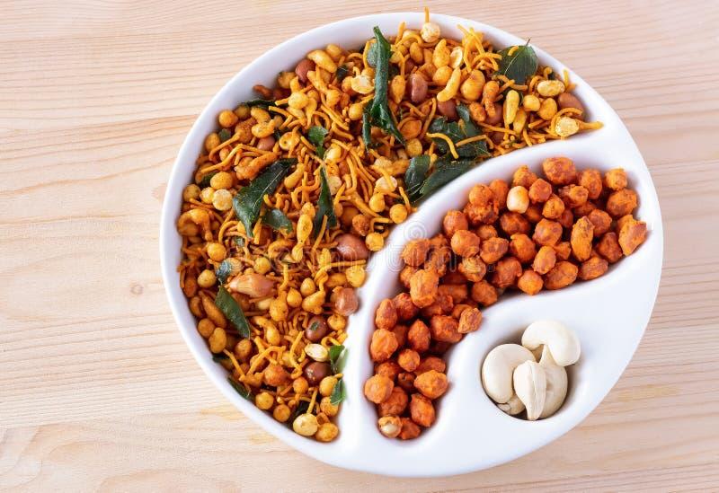 Mistura crocante picante indiana sul Nimco ou Namkeen e fundo de madeira da bacia branca revestida picante do amendoim isolado fotografia de stock