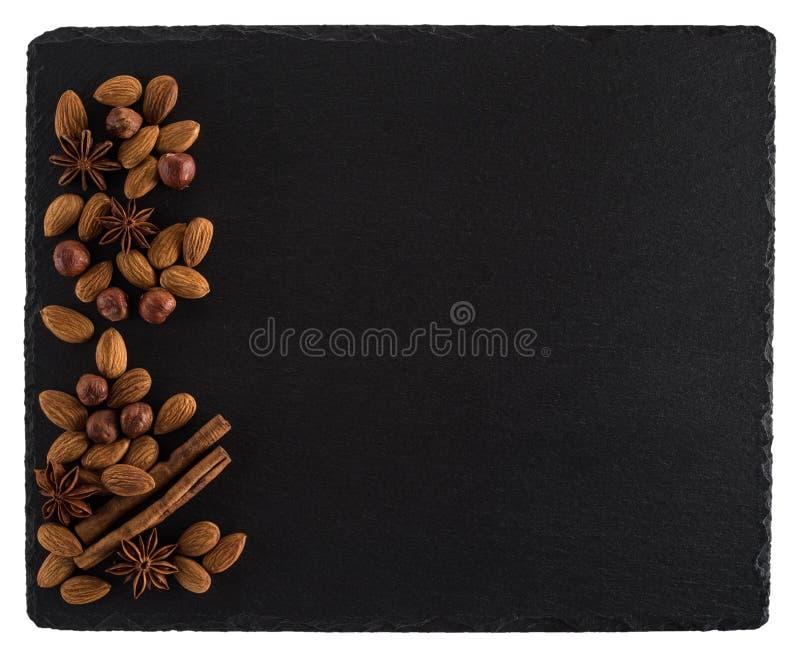 Mistura das porcas em uma placa preta da ardósia Isolado no fundo branco fotografia de stock royalty free