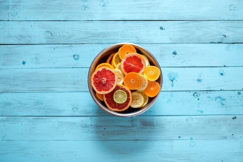 Mistura de citrinas maduras frescas em uma bacia em um fundo azul foto de stock