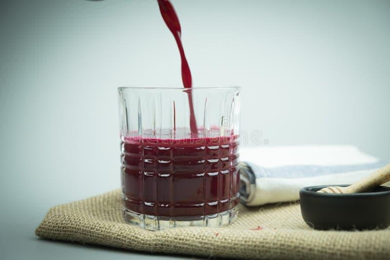 Mistura de derramamento do suco das beterrabas com gengibre e limão da garrafa imagens de stock royalty free