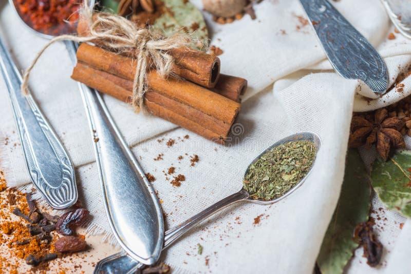 Mistura de especiarias e de ervas diferentes, cozinheiro e ingredientes da culinária na tabela com a decoração da folha de louro  imagem de stock royalty free