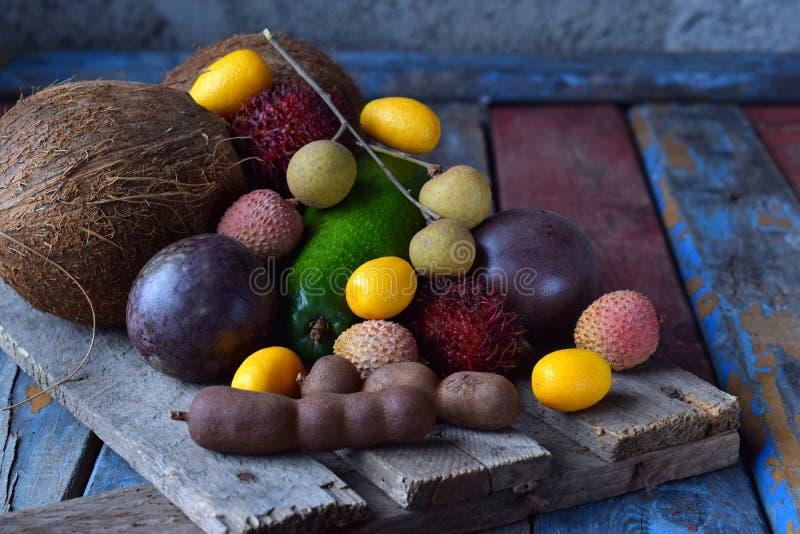 Mistura de frutos tropicais maduros com fruto de paixão, kumquat, lichi, rambutan, tamarindo, abacate, coco, olho do dragão em um fotos de stock royalty free