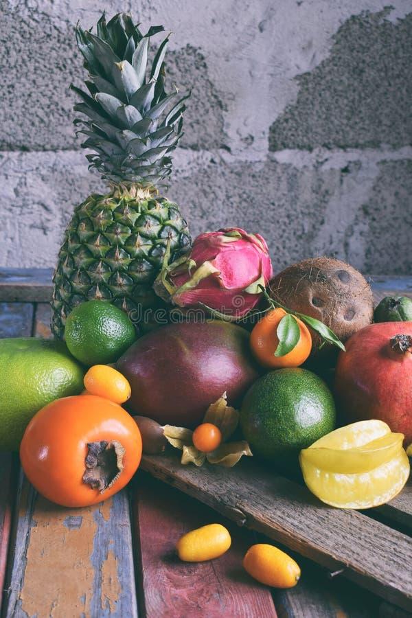 Mistura de frutos tropicais maduros com manga do abacate, kumquat, quivi, citrino Fundo de Superfood Alimento cru do vegetariano  foto de stock