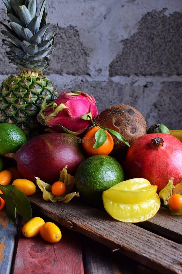 Mistura de frutos tropicais maduros com manga do abacate, kumquat, quivi, citrino Fundo de Superfood Alimento cru do vegetariano  fotografia de stock