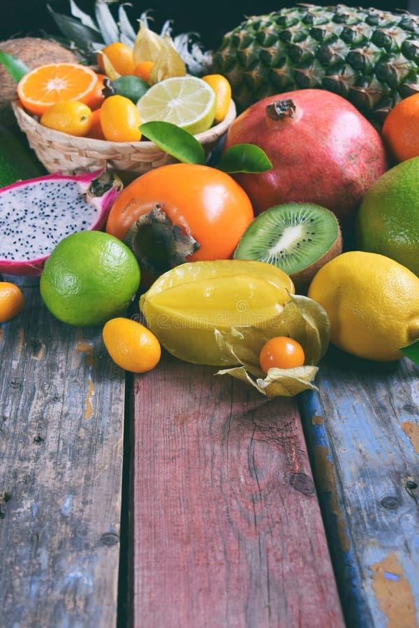 Mistura de frutos tropicais maduros com manga do abacate, kumquat, quivi, citrino Fundo de Superfood Alimento cru do vegetariano  imagem de stock