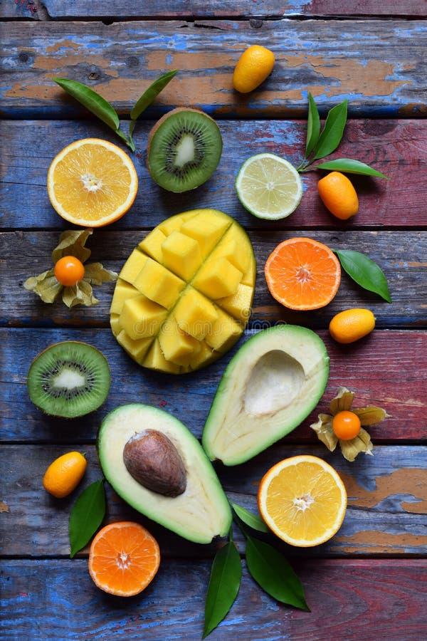 Mistura de frutos tropicais maduros com manga do abacate, kumquat, quivi, citrino Fundo de Superfood Alimento cru do vegetariano  imagens de stock royalty free