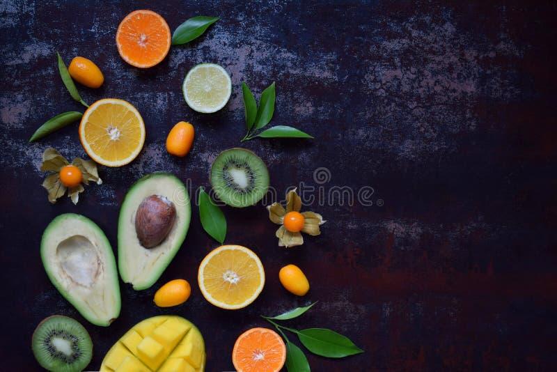 Mistura de frutos tropicais maduros com manga do abacate, kumquat, quivi, citrino Fundo de Superfood Alimento cru do vegetariano  foto de stock royalty free