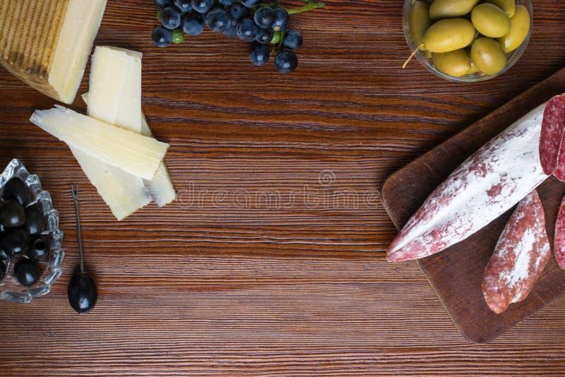 Mistura de petiscos e de aperitivos diferentes Tapas espanhóis em uma placa de madeira Tapas Bar chouriço, azeitonas, salsicha, q imagens de stock