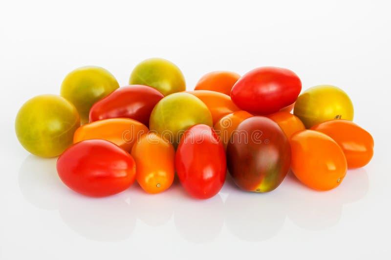 Mistura de tomates de cereja coloridos em um fundo lustroso branco Montão de tomates saborosos pequenos amarelos, alaranjados e v fotografia de stock royalty free