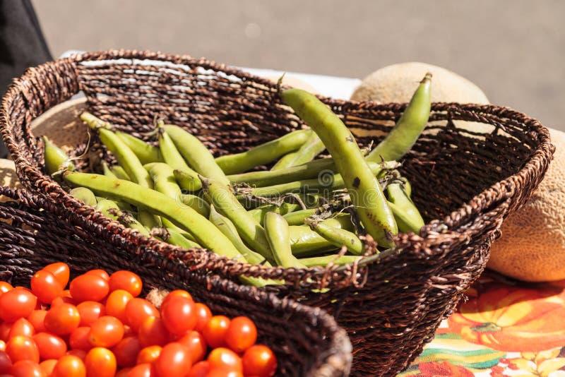 Mistura de tomates de cereja e de feijões de corda coloridos nas cestas foto de stock