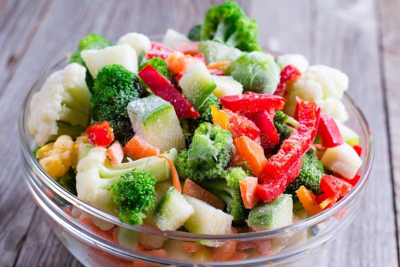 Mistura de vegetais congelados no vidro na tabela de madeira imagem de stock royalty free