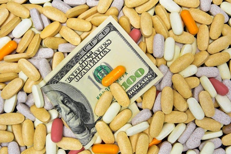 A mistura de vitaminas e os suplementos fecham-se acima com cem notas de dólar imagem de stock