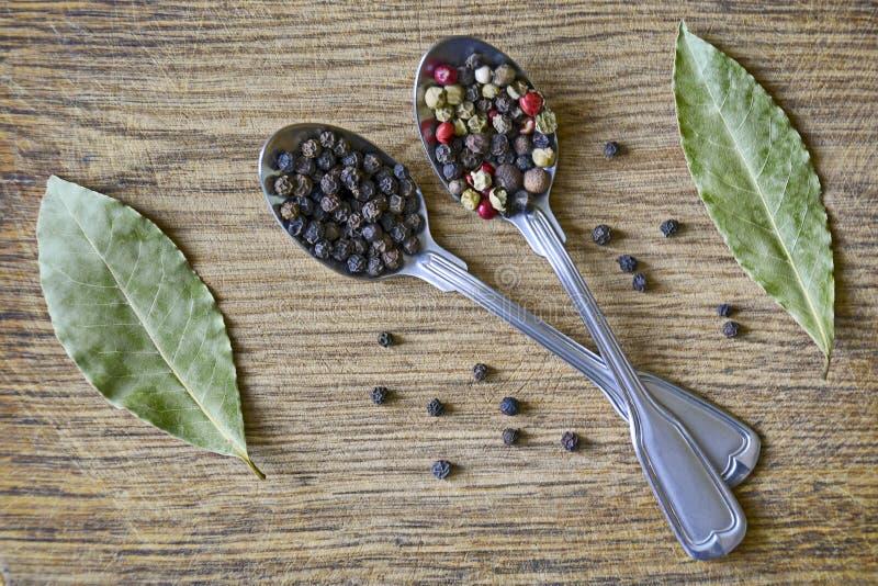 Mistura e grãos de pimenta da especiaria em colheres do metal e em folhas de baía secadas no fundo de madeira velho fotos de stock royalty free