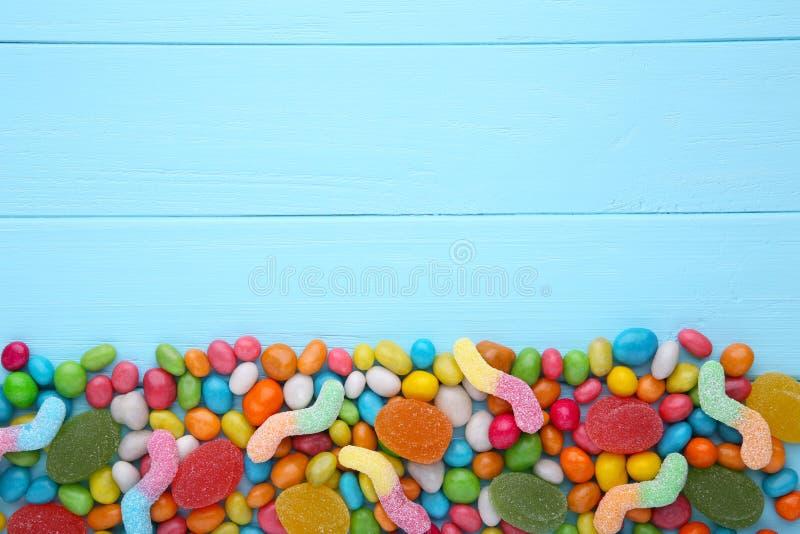 Mistura sortido de vários doces e geleias no fundo azul fotografia de stock