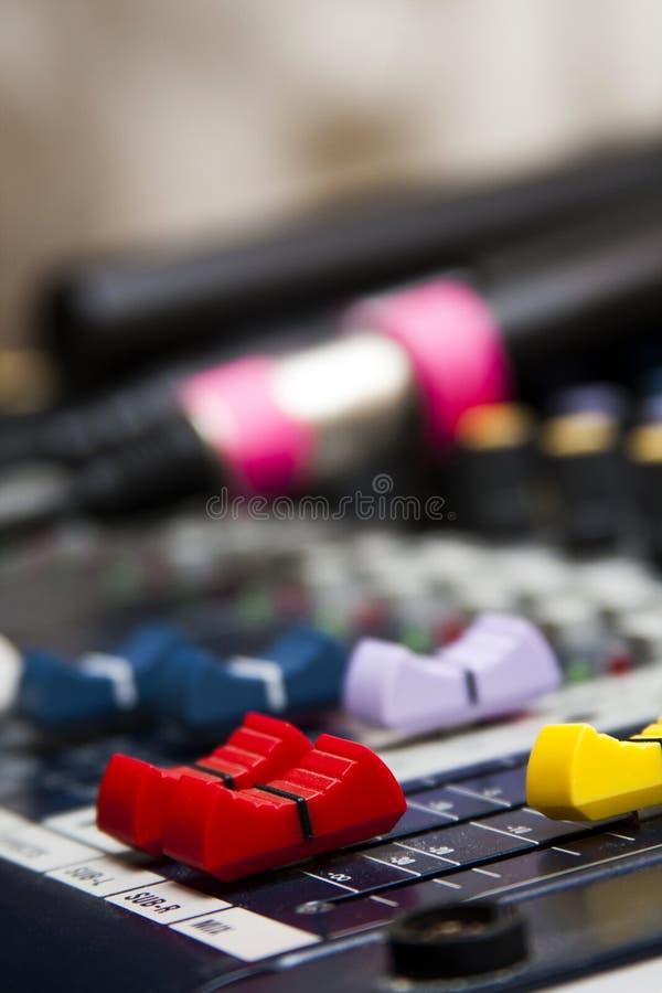 Misturador audio profissional com faders coloridos, microfones que encontram-se no fundo borrado fotografia de stock royalty free