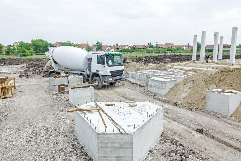 Misturador concreto que passa sobre o terreno de construção fotos de stock