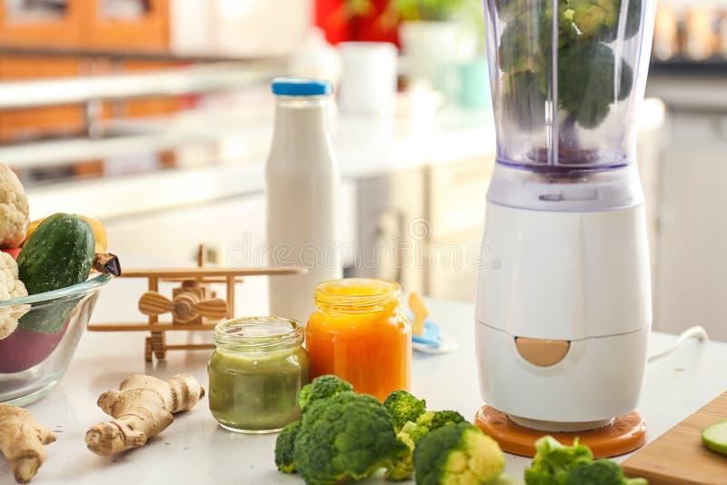 Misturador e ingredientes para o comida para bebê na mesa de cozinha fotografia de stock