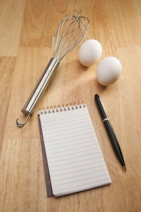 Misturador, ovos, pena e almofada de papel imagem de stock