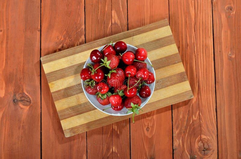 Misture bagas, cerejas e morangos frescas em uma tabela de madeira fotos de stock
